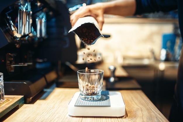 Mão de barista despeja grãos de café no copo