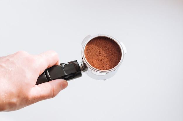 Mão de barista profissional segurando café moído em um porta-filtro para preparação.