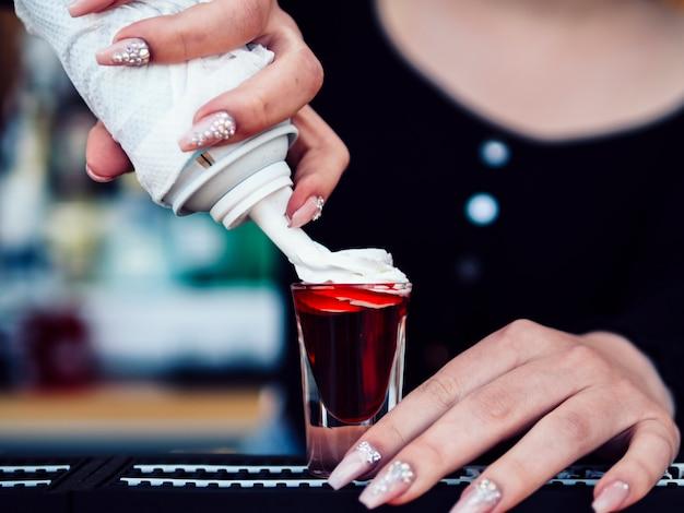 Mão de barman adicionando creme de leite para coquetel