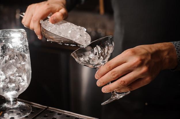 Mão de barman colocando gelo no copo de coquetel