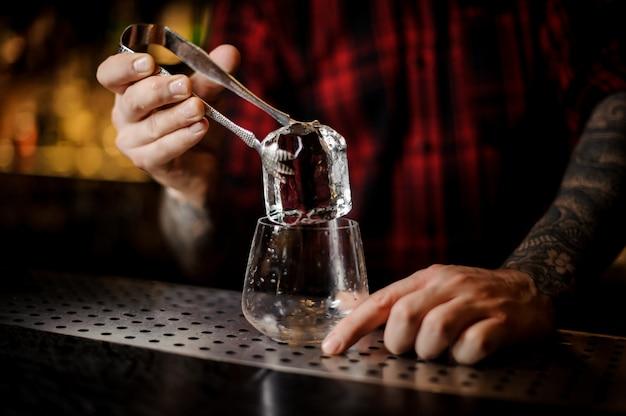 Mão de barman, colocando um cubo de gelo grande em um uísque dof