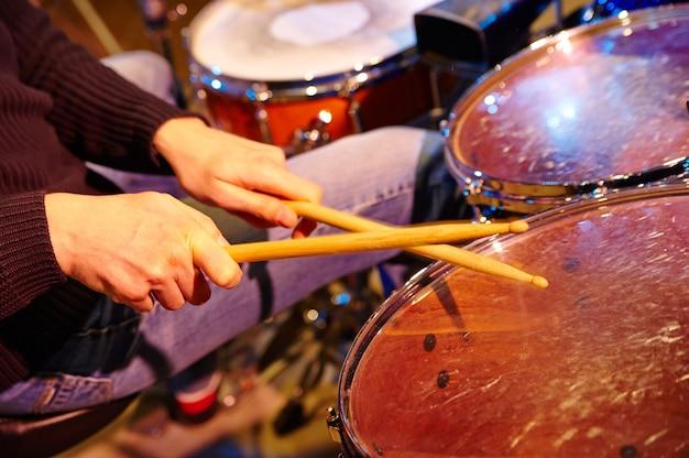 Mão de baterista com baquetas e bateria