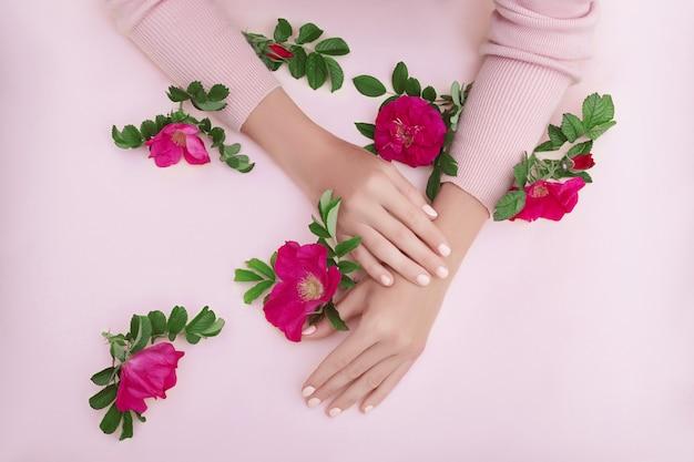 Mão de beleza de uma mulher com flores vermelhas situa-se na mesa em papel rosa