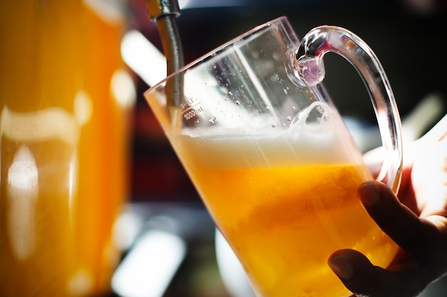 Mão de braga na torneira de cerveja derramando uma cerveja lager servindo no restaurante ou pub.