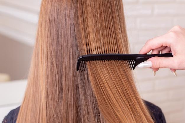 Mão de cabeleireiro escovando longos cabelos castanhos
