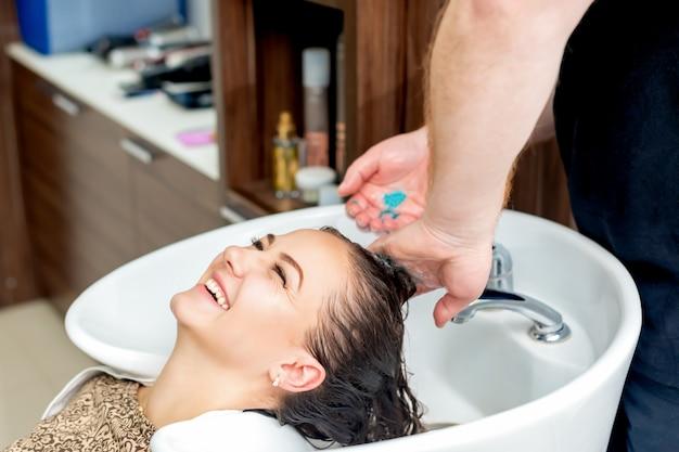Mão de cabeleireiro lavando o cabelo.