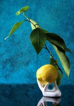 Mão de cerâmica segurando um limão