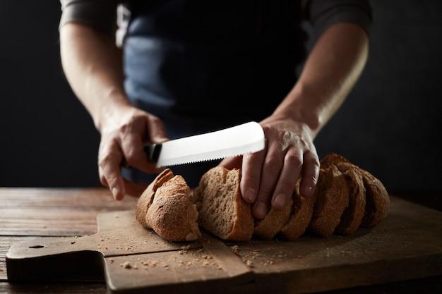 Mão de chef cortando pão fatiado caseiro