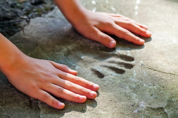 Mão de childs e impressão memorável em concreto