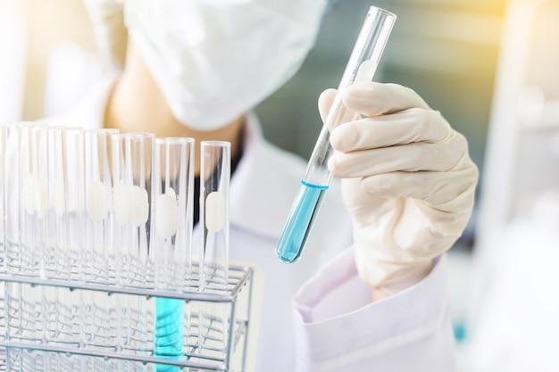 Mão de cientista segurando o tubo de ensaio de laboratório, pesquisa de laboratório de ciência e conceito de desenvolvimento