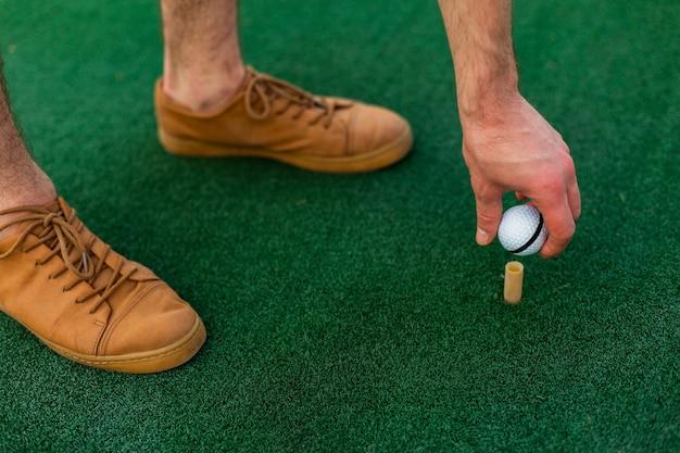 Mão de close-up, colocando a bola de golfe