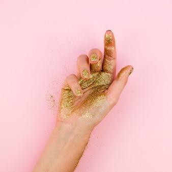 Mão de close-up com glitter dourado