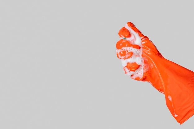 Mão de close-up com luva laranja
