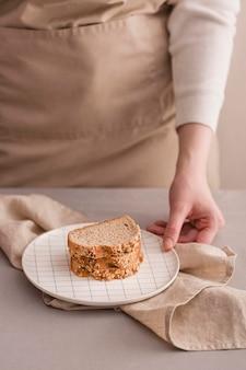 Mão de close-up com pão no prato