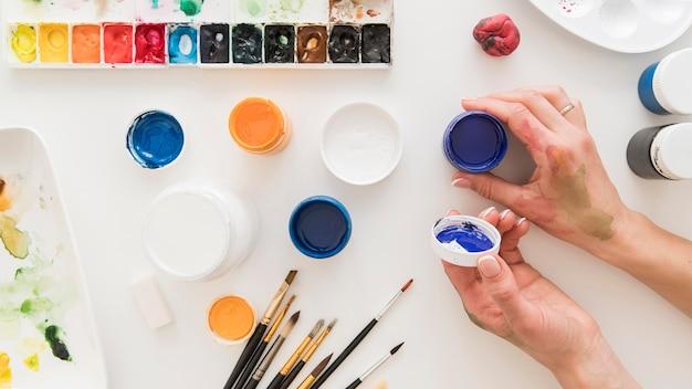 Mão de close-up com recipientes de tinta
