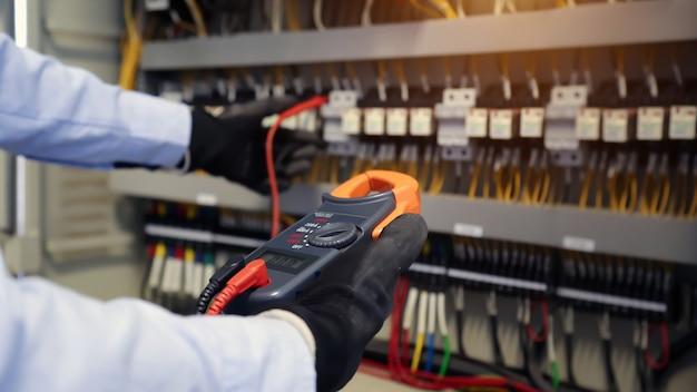 Mão de close-up de engenharia elétrica usando medição para verificação de eletricidade.
