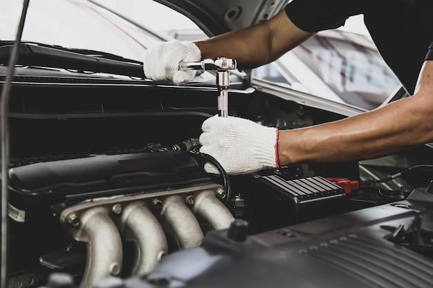 Mão de close-up de mecânico de automóveis usando a chave inglesa para consertar o motor de um carro.