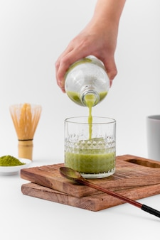 Mão de close-up, derramando chá matcha em vidro