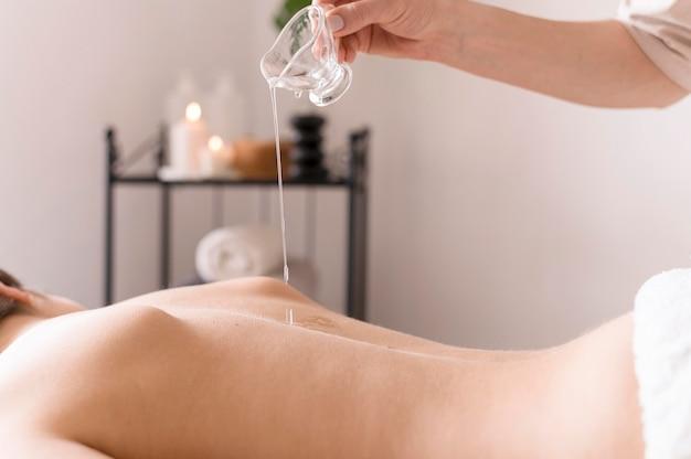 Mão de close-up, derramando óleo de massagem