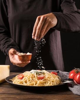 Mão de close-up, derramando queijo no macarrão