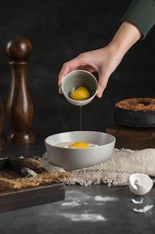 Mão de close-up, despejando ovos na tigela