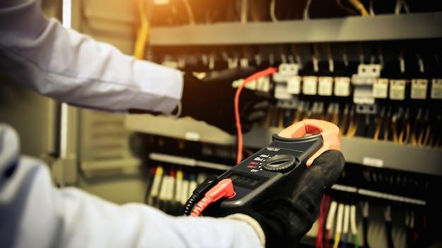 Mão de close-up do engenheiro elétrico usando equipamento de medição para verificar a tensão da corrente elétrica no disjuntor.