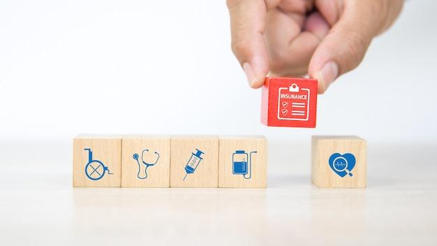 Mão de close-up escolhe bloco de madeira com ícone de seguro.