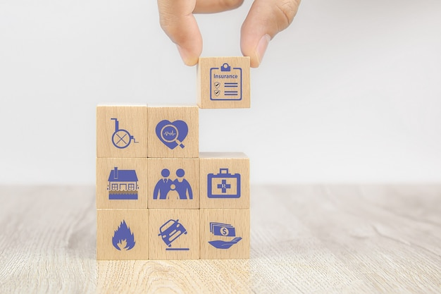 Mão de close-up escolhe blocos de brinquedo de madeira com ícone de seguro para seguro familiar