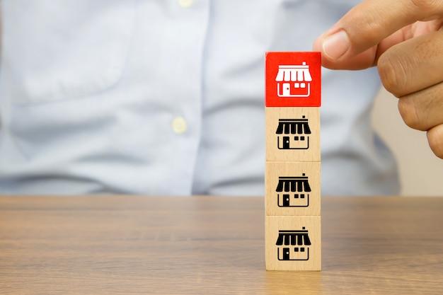 Mão de close-up escolhe blocos de brinquedo de madeira de cubo empilhados com o ícone da loja de negócios de franquia.