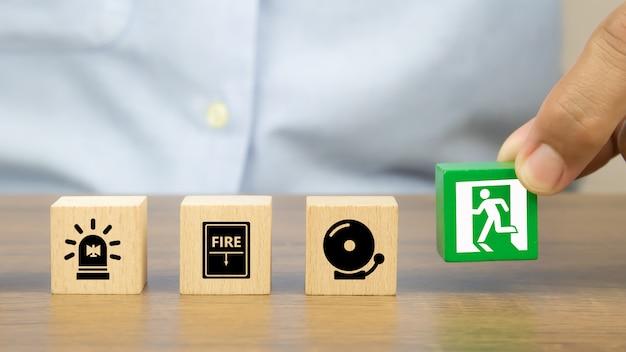 Mão de close-up escolhe blocos de brinquedo de madeira empilhados com ícone de saída de incêndio.