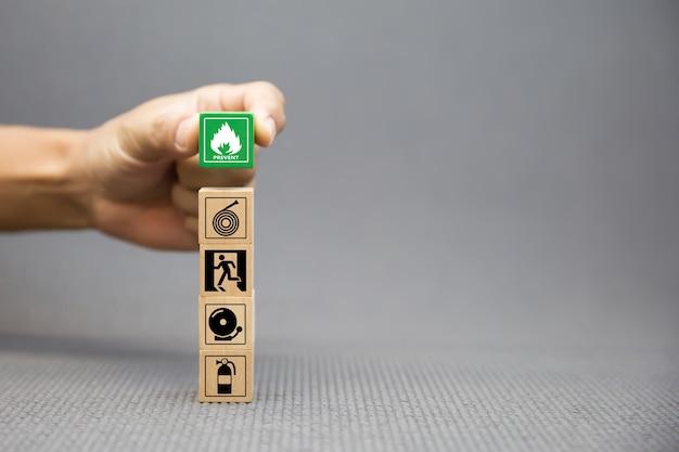Mão de close-up escolhe blocos de madeira com ícone de prevenção de fogo.