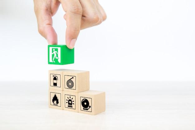 Mão de close-up escolhe blocos de madeira com sinal de saída de porta.