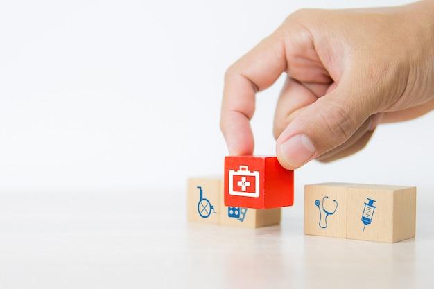 Mão de close-up escolhe blocos de madeira vermelhos empilhados com o ícone de uma sacola de remédios.
