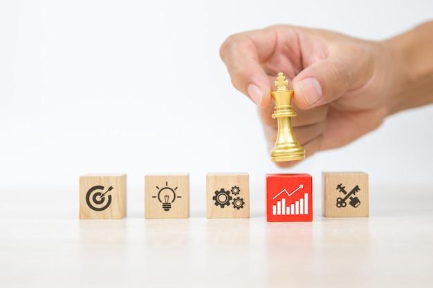 Mão de close-up escolhe xadrez rei em blocos de madeira empilhados com ícones de negócios