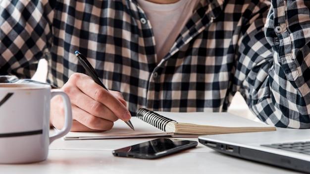 Mão de close-up, escrevendo no caderno