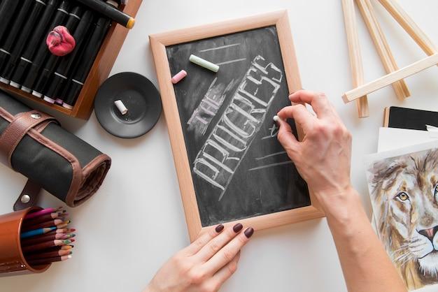 Mão de close-up, escrevendo no quadro-negro