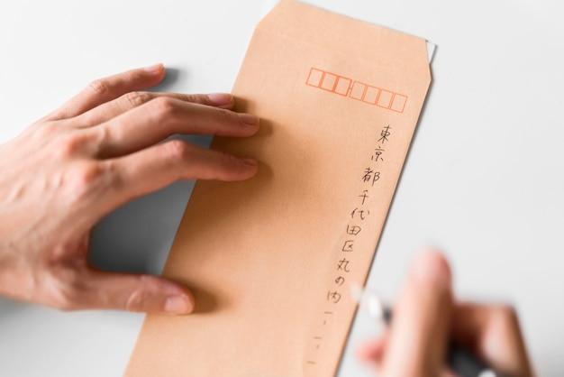 Mão de close-up escrevendo símbolos japoneses