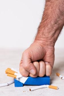 Mão de close-up, esmagando cigarros