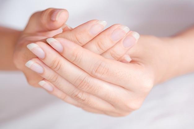 Mão de close-up ou unha de mulher no fundo desfocado, conceito de cuidados de saúde da unha. foco seletivo.