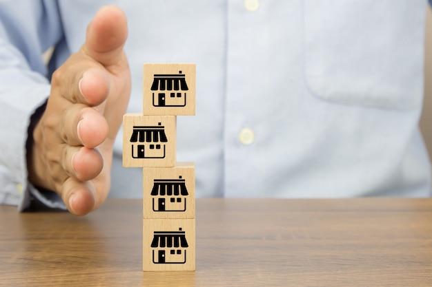 Mão de close-up para proteger os blocos de brinquedo de madeira do cubo empilhados com ícone de loja de negócios de franquia.