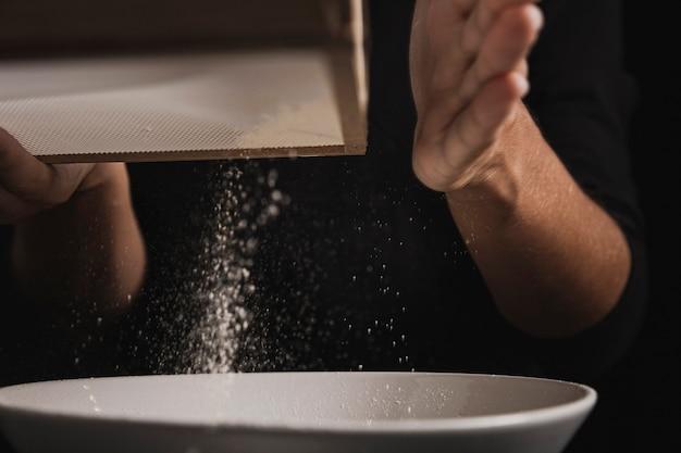 Mão de close-up, peneirar a farinha
