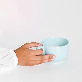Mão de close-up, segurando a caneca de cerâmica