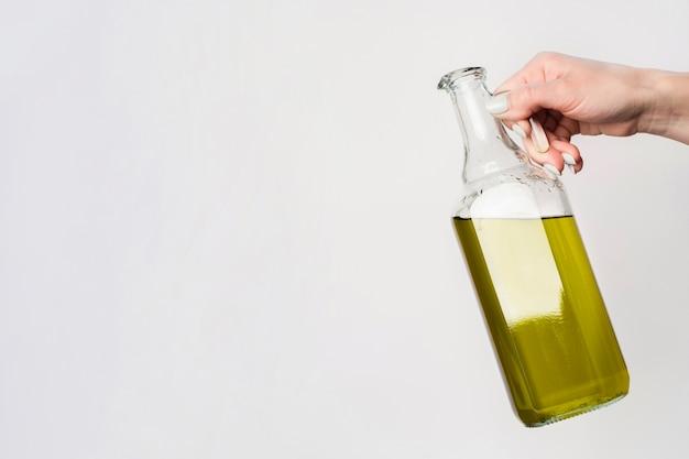 Mão de close-up, segurando a garrafa de óleo com espaço de cópia