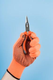 Mão de close-up, segurando um alicate