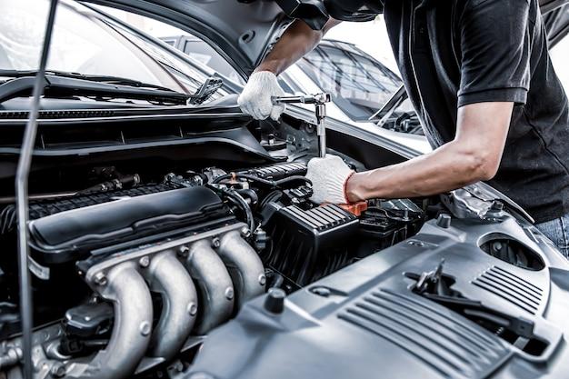 Mão de close-up usando a chave para consertar o motor do carro.