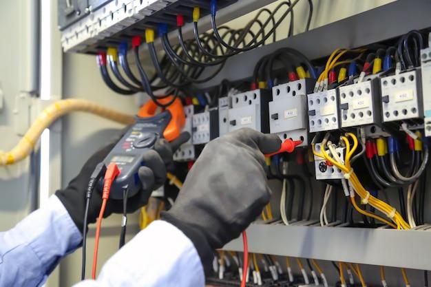 Mão de close-up usando a ferramenta de medição para verificar a eletricidade no disjuntor.