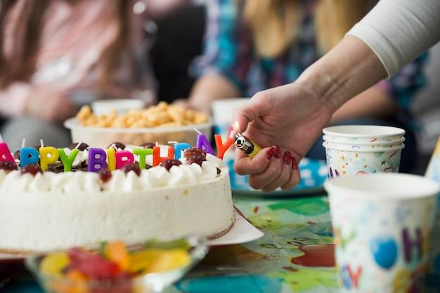 Mão de colheita acendendo velas no bolo de aniversário