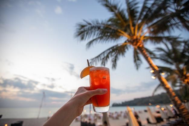 Mão de colheita com bebida na praia