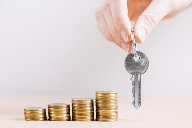 Mão de colheita com chave perto de dinheiro