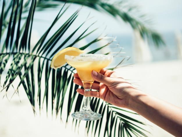 Mão de colheita com copo de bebida fresca